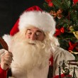 Portrait of Santa Claus answering Christmas letters — Stock Photo #32364573