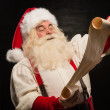 Portrait of happy Santa Claus reading Christmas letter — Stock Photo #32364665