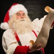 Portrait of happy Santa Claus reading Christmas letter — Stock Photo #32364699