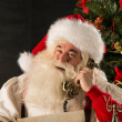 Santa Claus calling with vintage phone while reading an old roll — Stock Photo #32364745