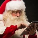 Santa Claus using tablet computer — Stock Photo #32364747