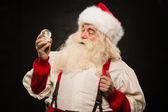 Santa Claus holding snow globe — Stock Photo