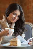 Woman reading a book at cafe — Stock Photo
