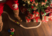 Unrecognizable Santa Claus playing with wooden railroad near Chr — Stock Photo