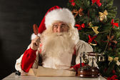 Portrait of Santa Claus answering Christmas letters — Stock Photo