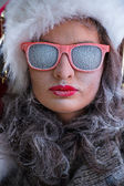 Woman wearing Santa Claus hat and sunglasses listening to music — Stock Photo