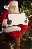 Santa claus sedět uvnitř, v tmavé místnosti u vánočního stromu a — Stock fotografie