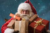 快乐圣诞老人户外在降雪携带礼品 t 的照片 — 图库照片