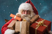 Photo of happy Santa Claus outdoors in snowfall carrying gifts t — Foto de Stock