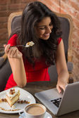 Young hispanic girl eating cake in the cafe while using her laptop — Stock Photo