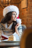 Beautiful young woman wearing Santa Claus red hat sitting at cafe — Stock Photo