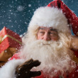 Santa Claus walking on the snow with his sack of gifts — Stock Photo
