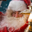Santa Claus is holding a shining lantern while sneaking to his home — Stock Photo #32857407