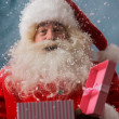 Stock Photo: Happy Santa Claus opening his Christmas gift at North Pole