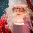 Portrait of happy Santa Claus opening gift box — Stock Photo
