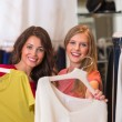 Two happy women shopping in clothes store — Stock Photo #32857705