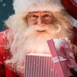 Happy Santa Claus opening his Christmas gift at North Pole — ストック写真
