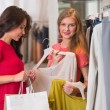 Stock Photo: Two happy women shopping in clothes store