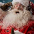Santa Claus is listening to music in headphones outdoors at North pole — Stock Photo #32857893