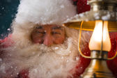 Santa Claus is holding a shining lantern while sneaking to his home — Stock Photo