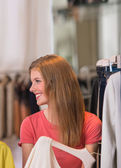 Authentic beautiful woman shopping in clothing store — Stok fotoğraf