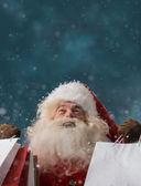 Santa Claus outdoors in snowfall holding shopping bags — Stock Photo