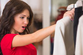 A female consumer shopping in an clothes store — Stock Photo