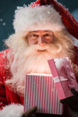 Happy Santa Claus opening his Christmas gift at North Pole — Stock Photo