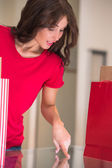 Smiling girl with shopping bags at store — Stock Photo