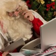 Santa Claus working on computer — Stok fotoğraf