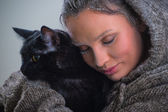 Woman holding black cat — Stock Photo