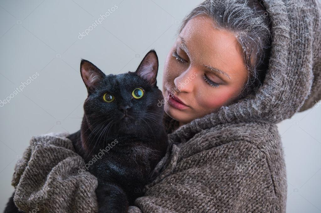 Winter portrait of young kind woman holding big black cat. Frost and snow on them — Foto di HASLOO - depositphotos_33877849-Woman-holding-black-cat