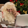 Santa Claus working on computer — Zdjęcie stockowe