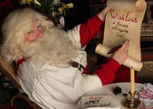 Santa Claus writing on old paper roll — Stock Photo