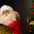 Santa Claus sitting in armchair — Stock Photo #34274367