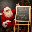 Santa Claus sitting near chalkboard — Stock Photo #34274509