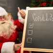 Santa Claus sitting near chalkboard — ストック写真