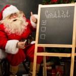 Santa Claus sitting near chalkboard — Stock Photo #34275603