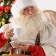 Santa Claus sitting in rocking chair — Stock Photo #34275817