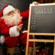 Stock Photo: Santa Claus near chalkboard