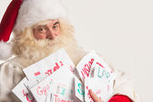 Santa Claus holding heap of letters — Stock Photo