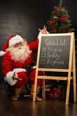 Santa Claus sitting near chalkboard — Stock Photo