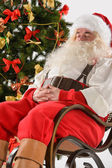 Santa Claus sitting in rocking chair  — Stock Photo