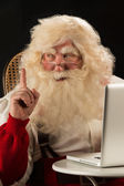 Santa Claus working on computer — Foto Stock