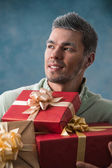 Young man carries a lot of presents — Stock Photo