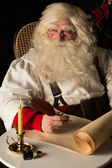 Santa Claus sitting at home and writing to do list — Stok fotoğraf