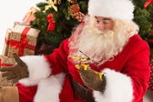 Santa Claus holding gift helicopter toy — Stock Photo
