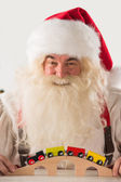 Santa Claus sitting and playing with railway toy — Stock Photo