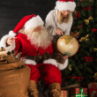 Stock Photo: SantClaus and his wife or helper holding globus and discussing
