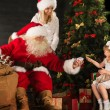 Photo of cute girl and her mother and Santa Claus at home — 图库照片